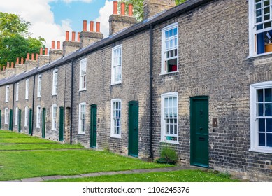 Row of restored Victorian brick houses with green colored doors on a local road in Cambridge, UK