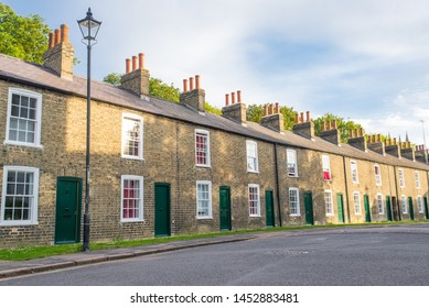Row of restored Victorian brick houses with green colored doors and white windows.
