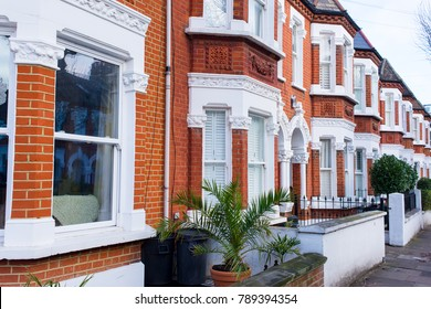 Row of restored Victorian house in red bricks and white finishing on a local street in Clapham, South London, UK
