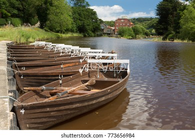 A row of rowing boats moored up on the river esk in North Yorkshire