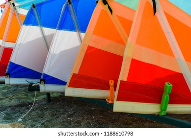 Row of the sail with mast for windsurfing is stacked side by side. Equipment for windsurfing on the beach.