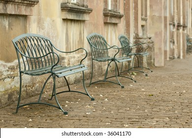 row of seating in an old cobbled courtyard