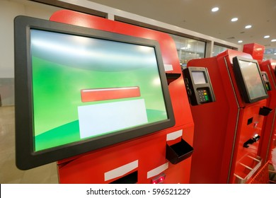 Row of self service cash desk with screen and payment terminal in modern supermarket