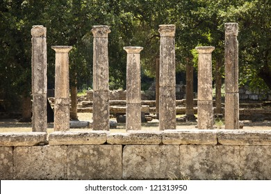 A row of seven classic Greek stone pillars are set in a line near the ancient city of Olympia in Greece.
