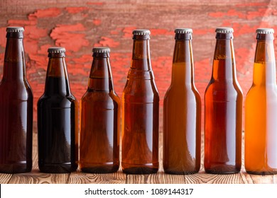 Row of seven types of beer in different shaped brown unlabelled bottles against a rustic wood background with peeling red paint
