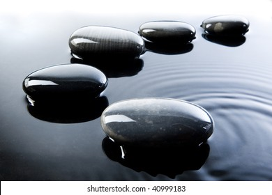 A row of shiny black pebbles in water