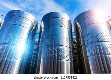 Row of the shiny stainless steel storage tank containers at the chemical plant factory against blue sky with clouds