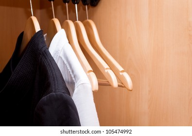 A row of shirts hanging in the closet.