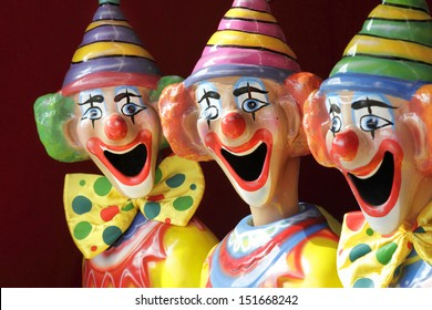 A row of sideshow carnival game clowns with mouths open.  Focus to middle clown.