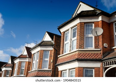 A row of similar refurbished Edwardian houses with red brick facade and bay windows. Typical British architecture. Sunny weather and blue sky in the background. Finchley, London, UK. 29012021
