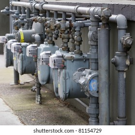 Row of Six gray gas meters manifolded together next to a building