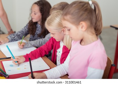 Row of small children in art class at school sitting at a long desk drawing with colored pencil crayons, focus to a young girl in the foreground