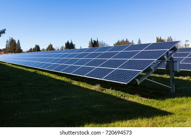 Row of solar panels on a grassy field under sunlight.