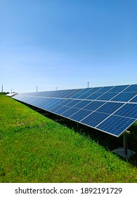 A row of solar panels stand on green field, against the blue sky. A symbol of clean energy, concern for the environment, a concept.