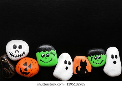 A row of spooky cartoon halloween painted rocks are lined up and isolated along the bottom border of a black background with copy-space.