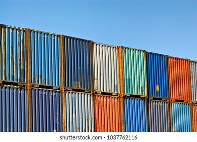 A row of stacked shipping containers against a blue sky.