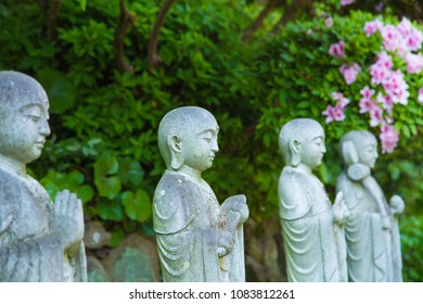 Row of statues in garden surrounded by foliage.