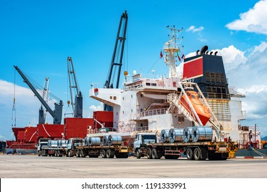 row of steel coils on the trailer lorry standing by and ready to takes loading to the ship, export and transports for sea and land meet together in sea port terminal, logistics services to Worldwide