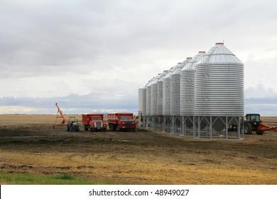row of steel grain bins dwarfing grain trucks and tractors
