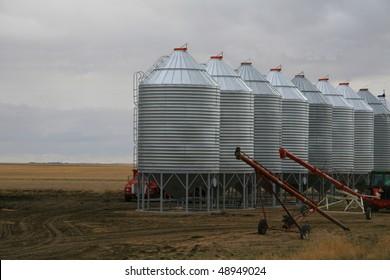 row of steel grain bins with two grain augers