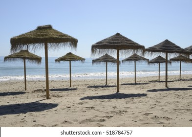 Row of straw umbrellas in the beach of  Marbella, Andalusia, Spain.