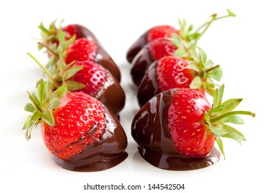 Row of strawberries dipped in delicious chocolate isolated on the white background