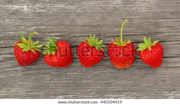 Row of strawberry on wood desk with soft shadows