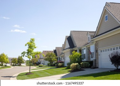 A row of strikingly similar mass-construction homes lines a curved road ending in a cul-de-sac and set against a blue sky with a few small clouds. Bushes and small trees decorate the landscape.