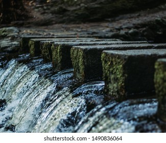 A row of symmetrical stepping stones covered in moss crossing a river with a small waterfall at the end.