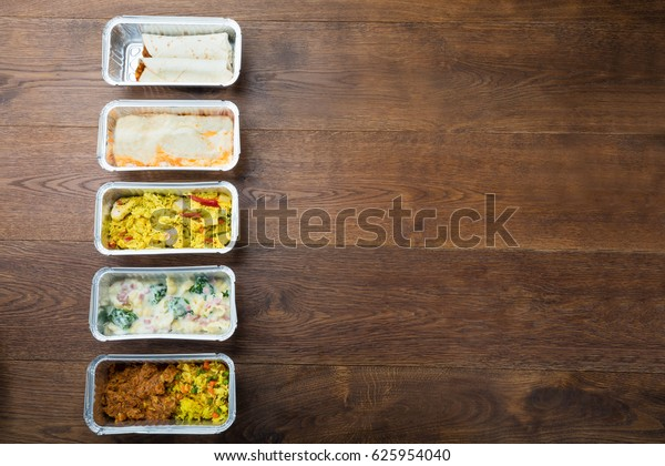 Row Of Take Away Dishes In Foil Container On Wooden Table