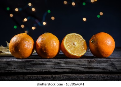 A row of tangerines on a barn wood board with background lights on a black background