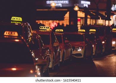 Row of taxi. Night transportation in urban city. Illuminated scene after dark. Downtown munich taxi cars to transport tourist. Bokeh background.