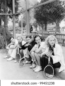 Row of tennis players with rackets