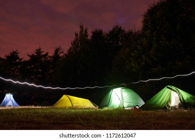 A row of tents lit up by lights sit in a field beneath trees as a headtorch trail passes around them.