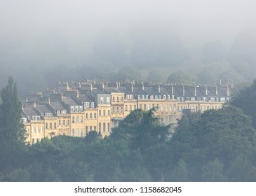 A row of terraced Georgian buildings shrouded in morning mist  in Bath, UK