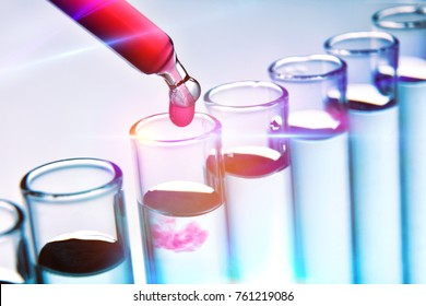 Row of test tubes and dropper with red solution and blue background. Scientific research with substances.. Elevated view