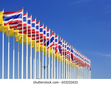 Row of Thailand nation flag and King Rama IX flag in the blue sky background