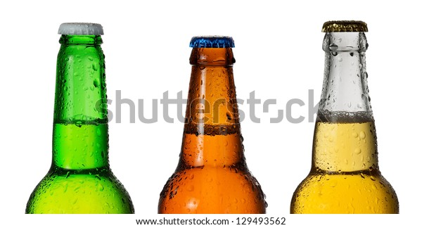 Row of three beer bottles in different colors isolated on white background