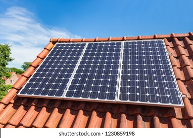 Row of three blue solar collectors  on roof of house