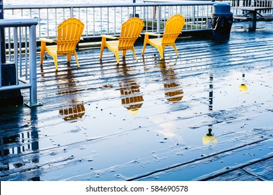 A row of three bright yellow chairs in contrast to the slick, rainy harbor boardwalk , tables, and ocean waves around them.
