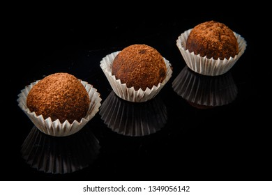 row of three healthy useful organic handmade round chocolate candies decorated with brown cocao powder on black mirror background