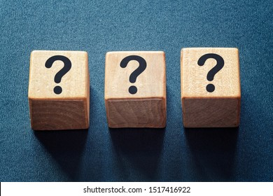 Row of three question marks on wooden blocks viewed high angle centered on a textured blue background