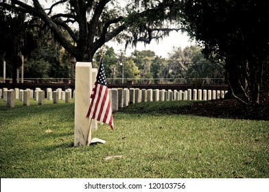 Row of tombstones at Beaufort National Cemetery in South Carolina, with American Flag in ground of first grave site