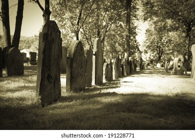 A row of tombstones in a very old cemetery; photo done in halloween or seasonal colortones