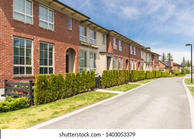 Row of town homes in the suburbs of Canada on a sunny day. Beautifully done landscaping with nicely manicured front yard.
