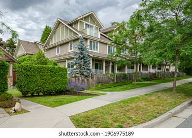 Row of townhouses with concrete pathway in front on couldy day in Vancouver, BC
