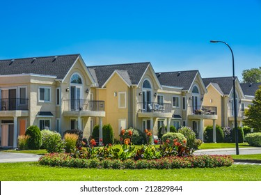 A row of townhouses on street with road and flower land in front. Townhouses on sunny day in British Columbia