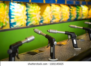 Row of toy water pistols for a carnival shooting game, at a boardwalk midway, with space for text on top