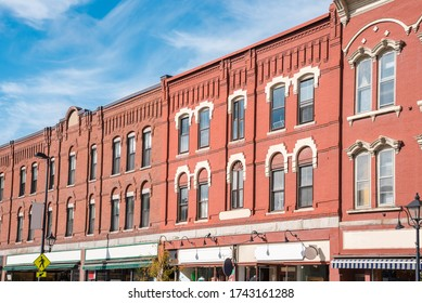 Row of traditional American redbrick buildings with shops on ground level on a sunny autumn day