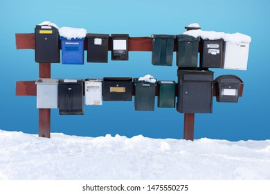 Row of traditional letter boxes in winter, on bright blue sky